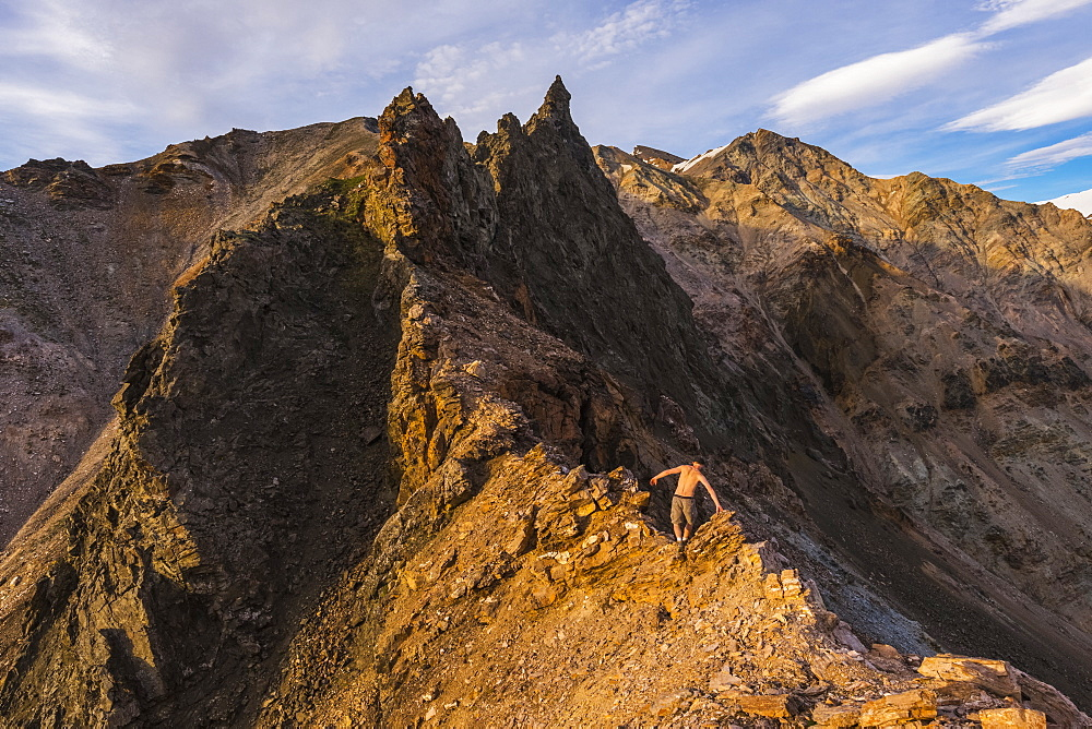 A shirtless hiker scrambles over a craggy ridge in the eastern Alaska Range near Whistler Creek in summer; Alaska, United States of America