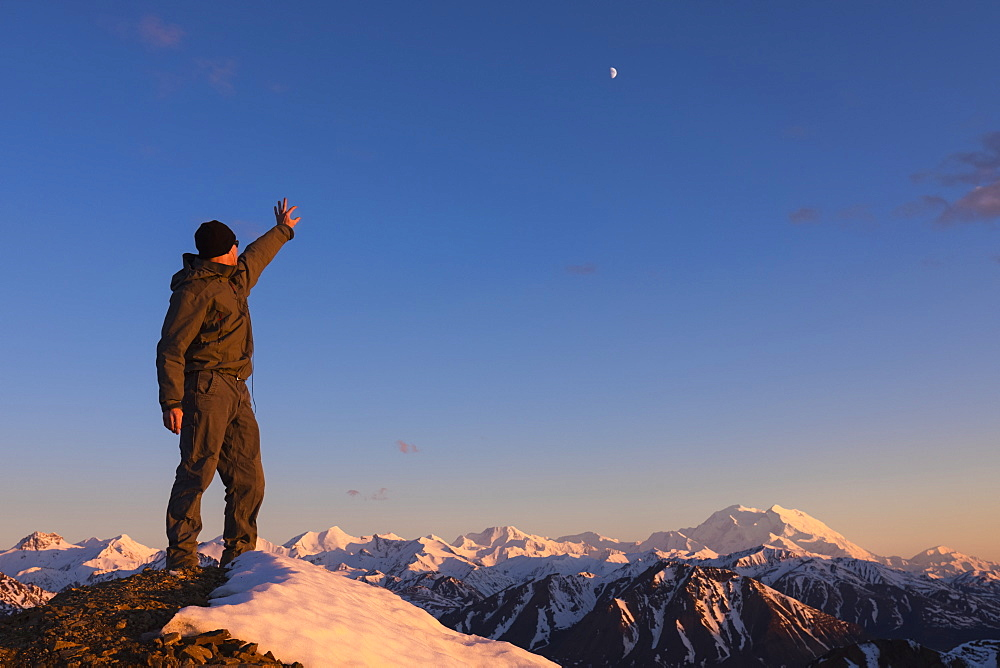 A man points at the moon hanging over Denali from the top of a snowy ridge at sunset near Polychrome Mountain in Denali National Park; Alaska, United States of America