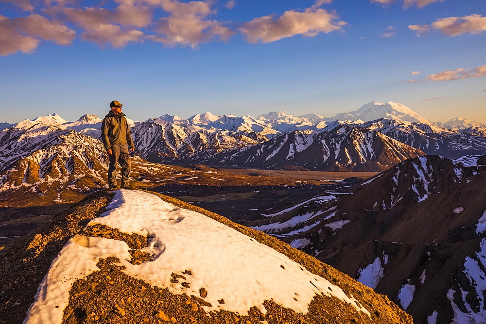 A man on a snowy ridge near Polychrome Mountain in Denali National Park faces the sunset with Denali in the background; Alaska, United States of America - 1116-39581