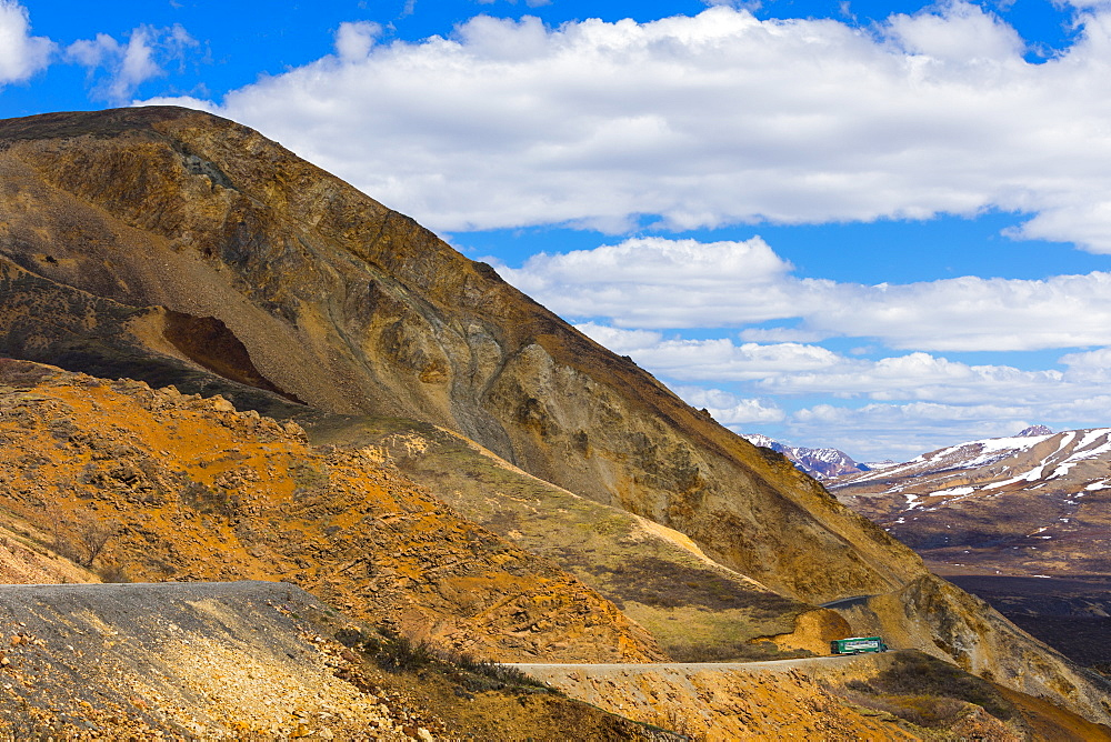 A shuttle bus winds around cliffs near Polychrome Pass in Denali National Park; Alaska, United States of America