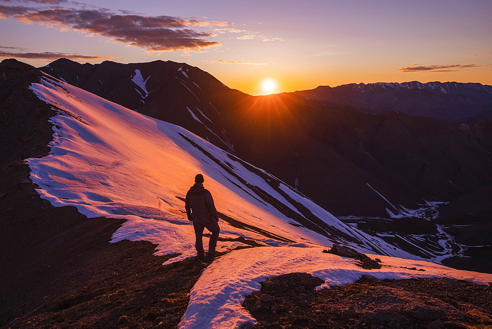 A man stands silhouetted on a ridge as the sun sets behind Polychrome Mountain in Denali National Park in early summer; Alaska, United States of America