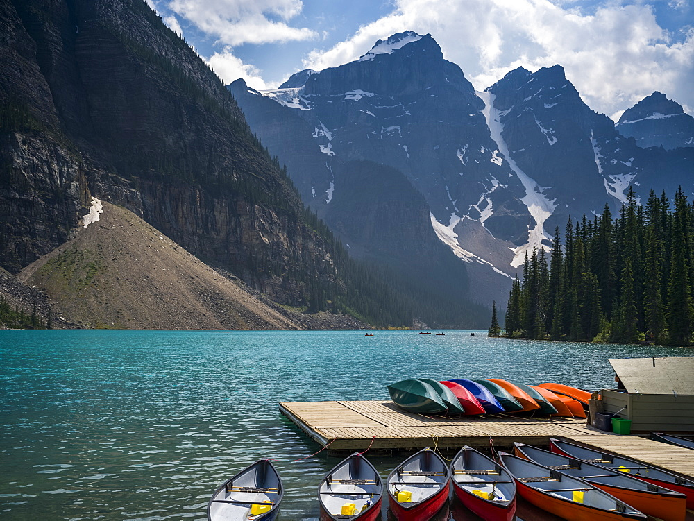Canoes in the water and sitting on a dock along the shore of Moraine Lake in the Canadian Rocky Mountains; Eldon, Alberta, Canada