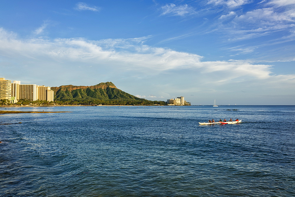 Tourists paddle in an outrigger canoe at Waikiki with Diamond Head in the distance, Waikiki, Oahu, Hawaii, United States of America