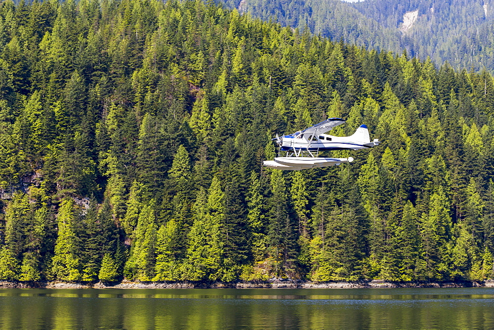 A float plane travels low above the ocean on a scenic tour of the forest and mountains near Vancouver, British Columbia, Canada