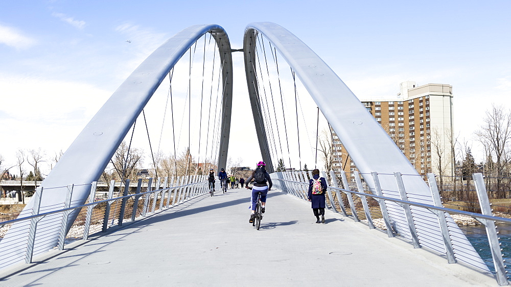 Pedestrians and cyclists going across a bridge over the Bow River, Calgary, Alberta, Canada