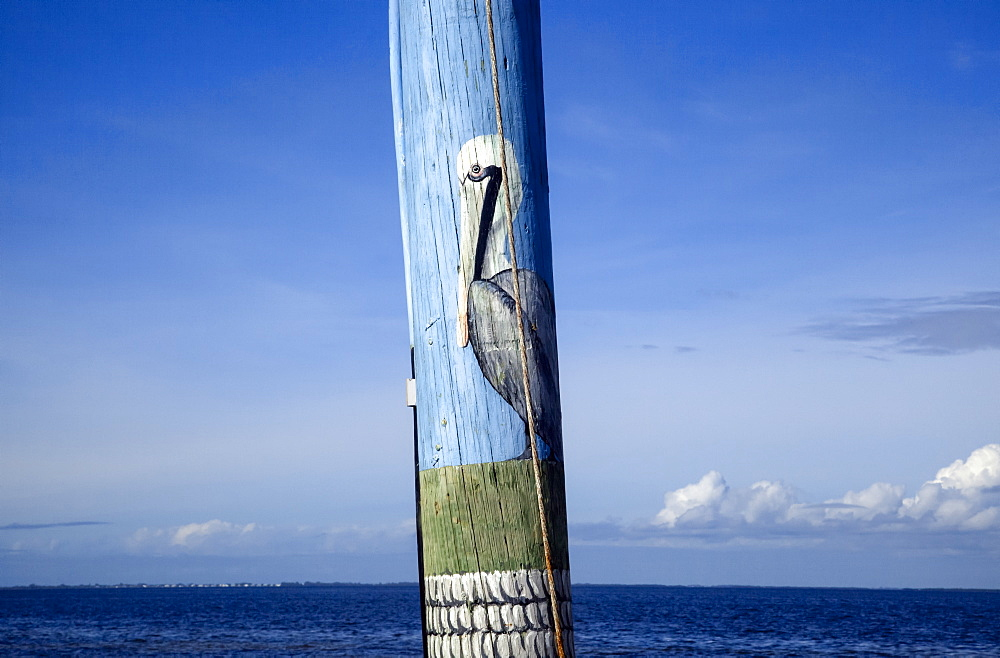 Close-up view of a pelican painted on a telephone pole with ocean and blue sky beyond, Pine Island, Florida, United States of America