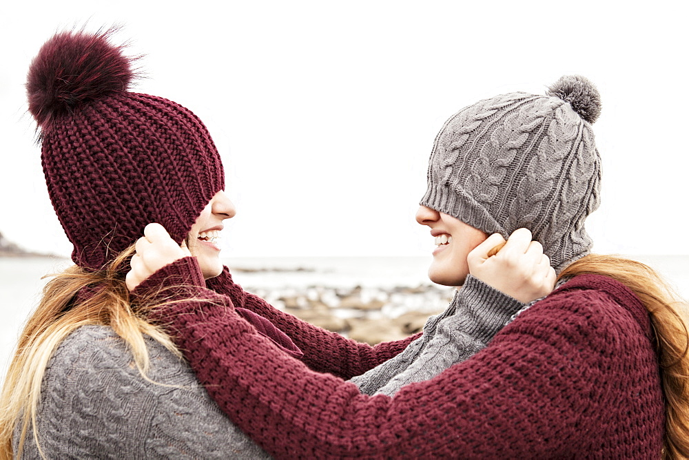 Two friends playing on the beach wearing knit hats and scarves, Woodbine Beach, Toronto, Ontario, Canada
