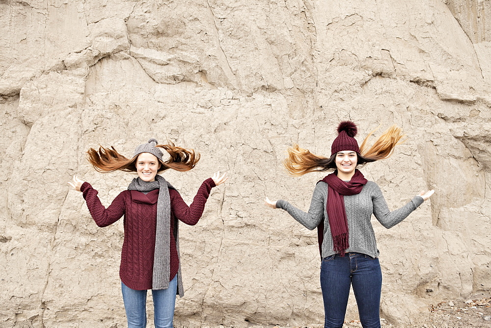 Two friends standing in front of the Scarborough Bluffs and flipping hair up, Scarborough, Ontario, Canada