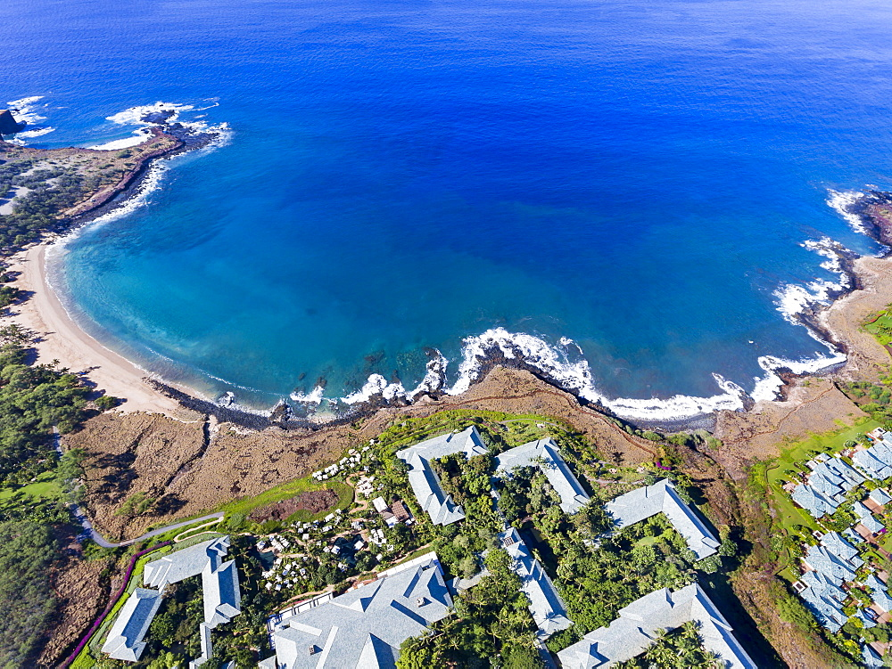 An aerial view of the golden beach and palm tree's at Hulopo'e Beach Park, and the Four Seasons resort at Manele Bay, Wailuku, Lanai, Hawaii, United States of America