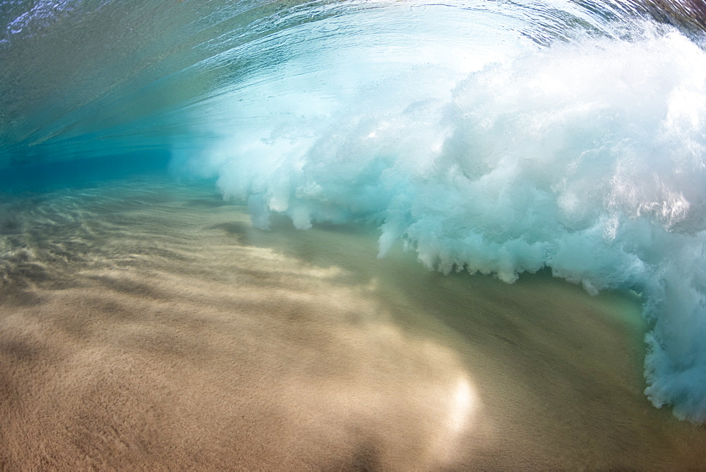 Underwater view of a breaking wave as the surf crashes over a sandy bottom off the island of Maui, Maui, Hawaii, United States of America