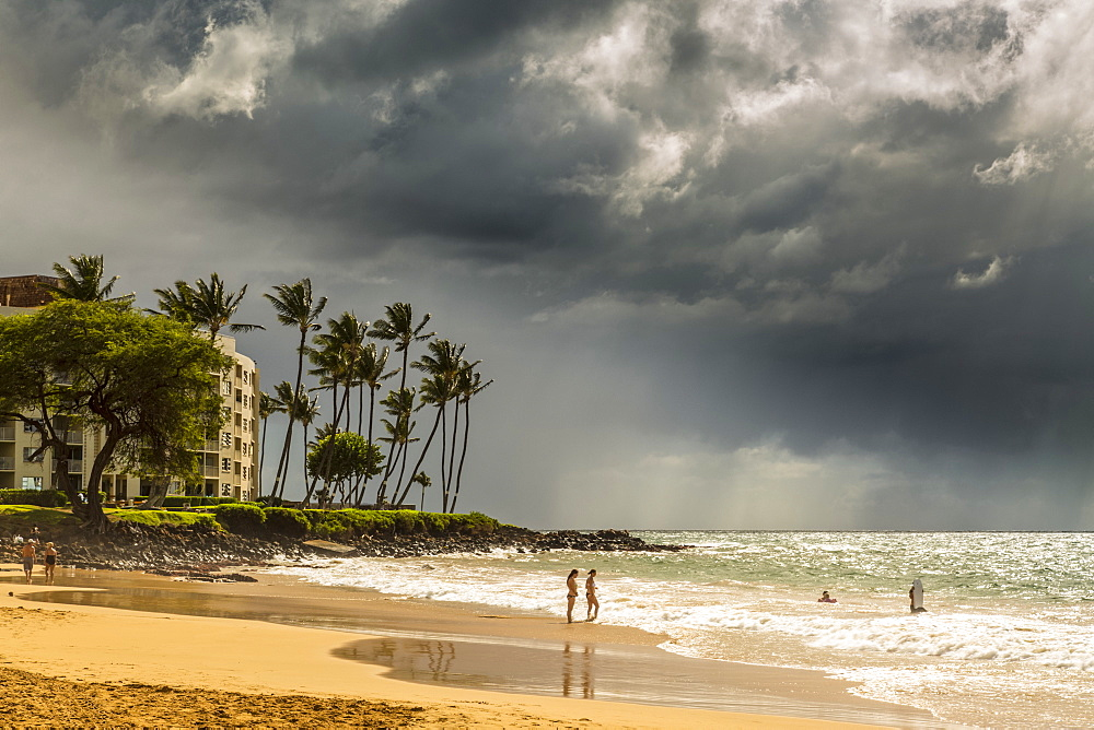 Tourists on a beach on the island of Maui with dark clouds and rainfall over the ocean in the distance, Makawao, Maui, Hawaii, United States of America