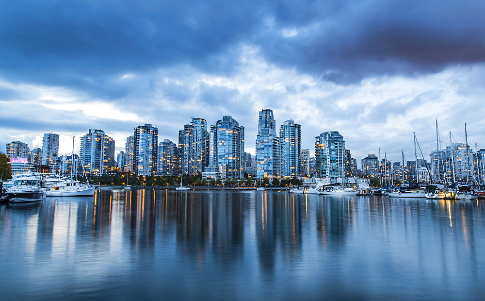 Skyline of residential buildings along the waterfront with boats in the harbour at dusk, Vancouver, British Columbia, Canada
