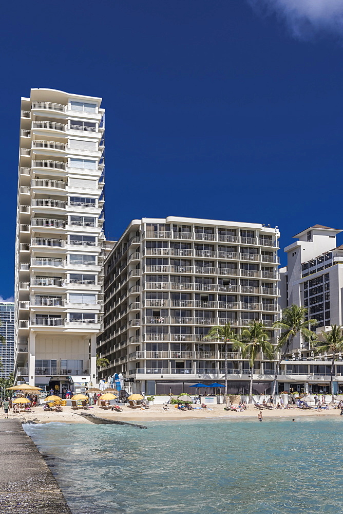 Castle Waikiki Shore (left), Outrigger Reef Waikiki Beach Resort (center), and Halekulani Hotel (far right) on Waikiki Beach, Waikiki, Honolulu, Oahu, Hawaii, United States of America