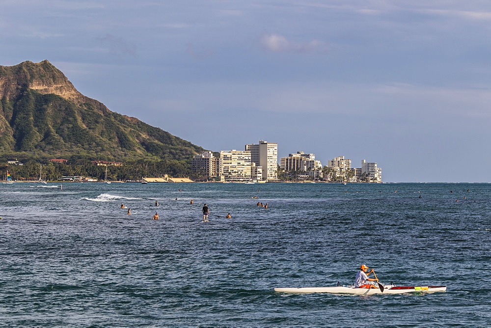 View of Diamond Head, Waikiki, and the two major Hawaiian watersports outrigger canoeing and surfing, from Magic Island, Ala Moana Beach Park, Honolulu, Hawaii, United States of America