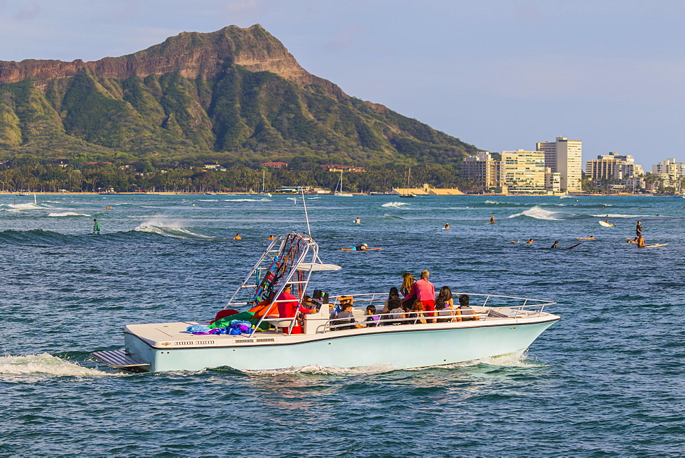 View of Diamond Head, Waikiki, a Hawaiian Parasail boat and surfing from Magic Island, Ala Moana Beach Park, Honolulu, Oahu, Hawaii, United States of America