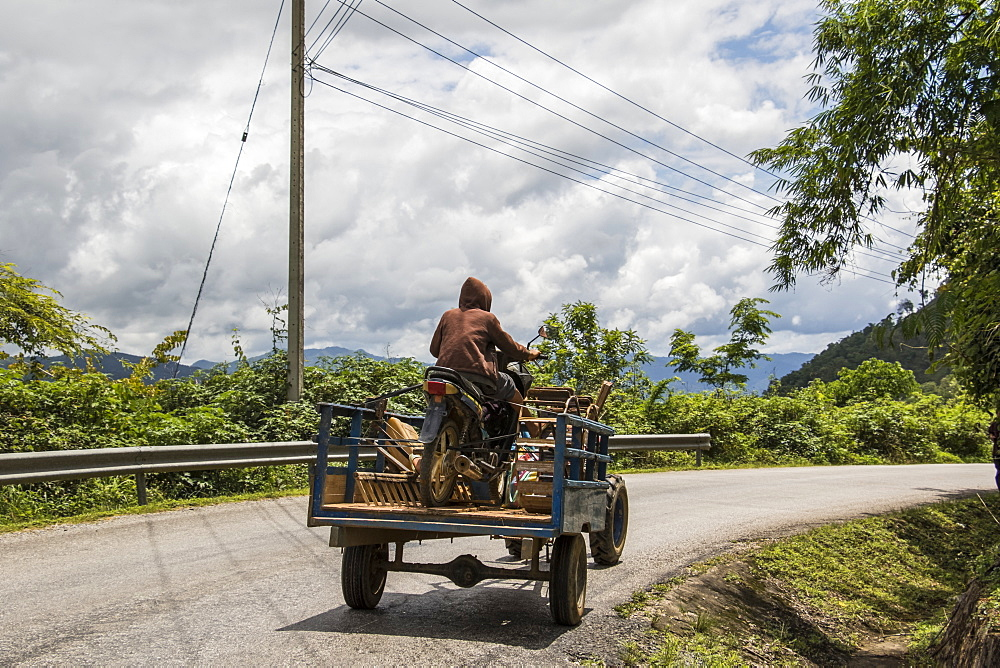 Man driving a tractor carrying a motorcycle near Muang Kham, Xiangkhouang, Laos