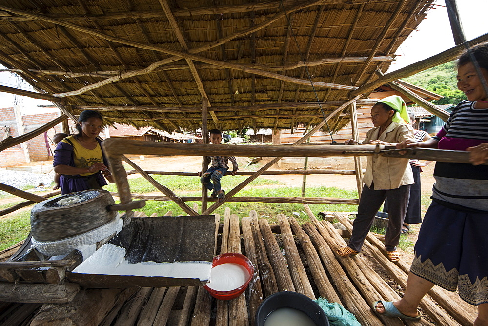 Hmong women grinding rice for the production of rice paper in Na Kam Peng, also called Bomb Village, Xiangkhouang, Laos