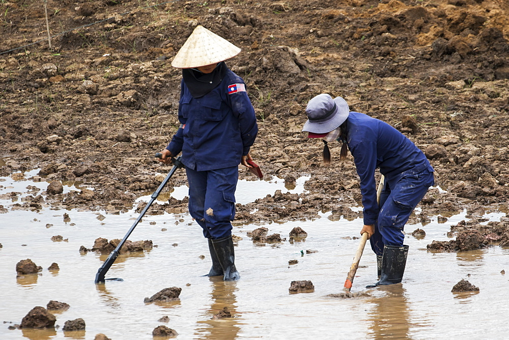 Women using a metal detector while clearing landmines in a field near Phonsavan, Xiangkhouang, Laos