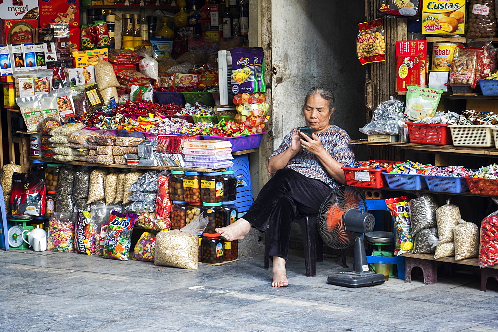 Female vendor sitting outside her shop with bare feet using her smart phone, Hanoi, Hanoi, Vietnam