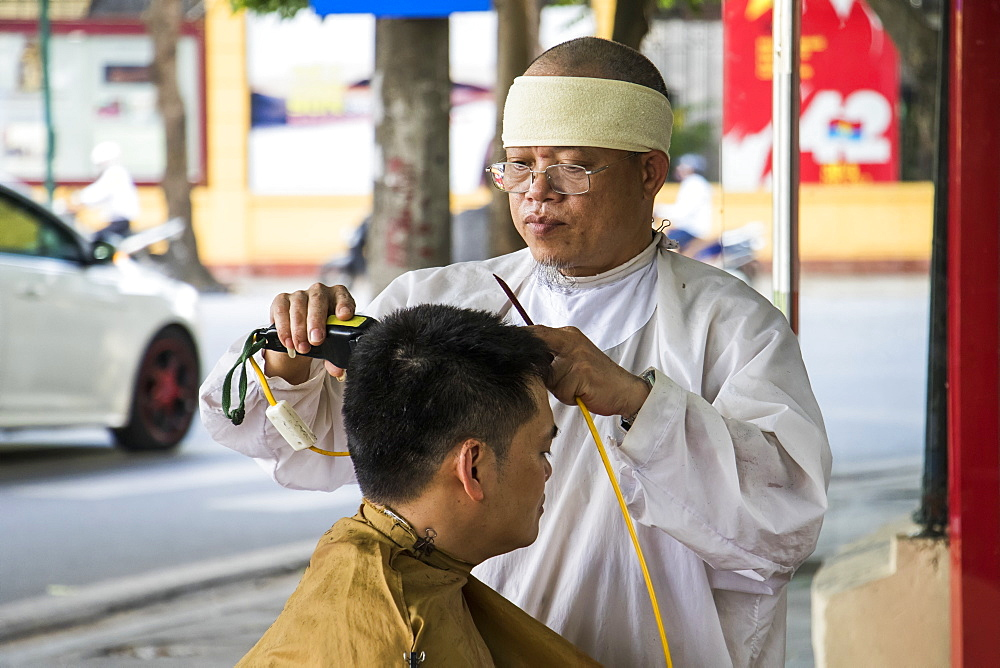 Street barber giving a haircut in the Old Quarter, Hanoi, Hanoi, Vietnam