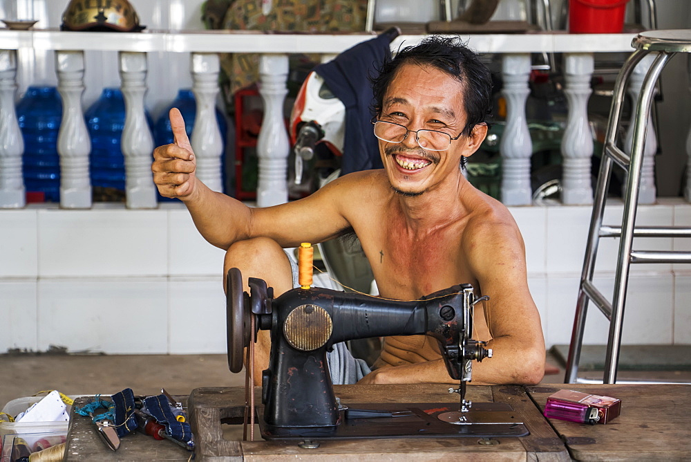Tailor, shirtless and sitting by his sewing machine giving the thumbs up with a smile, My Long, Mekong Delta, Tien Giang, Vietnam