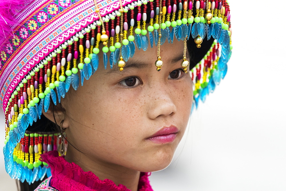 Portrait of a young Hmong girl wearing a colourful, decorative hat, Sapa, Lao Cai, Vietnam