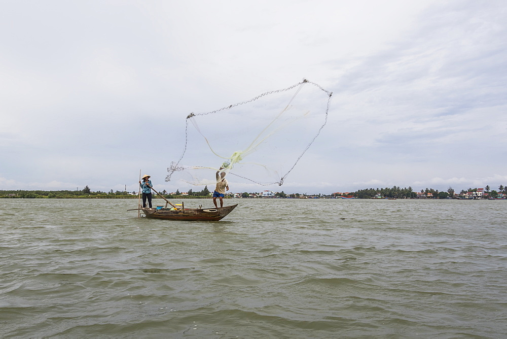 Fisherman throwing a net from a boat, Hoi An Ancient Town, Quang Nam, Vietnam