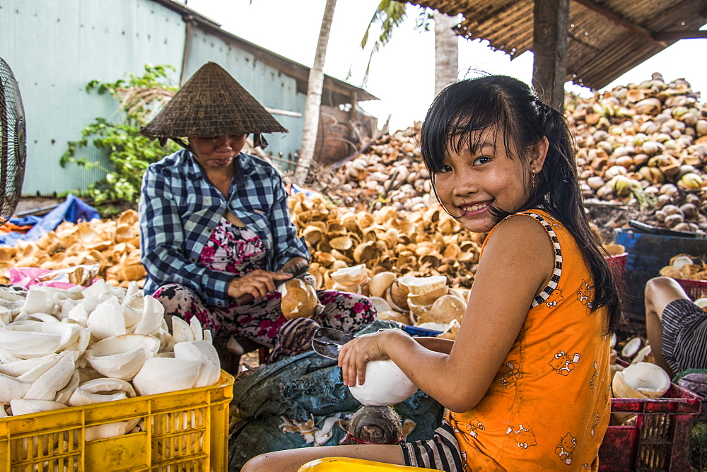 Girl and woman at a coconut processing family owned business in the Mekong Delta, Ben Tre, Vietnam