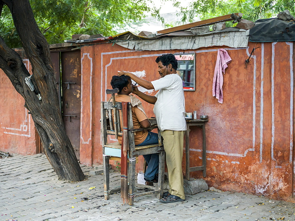 A man shaving another man's face with a set up of table and chair along the street, Jaipur, Rajasthan, India