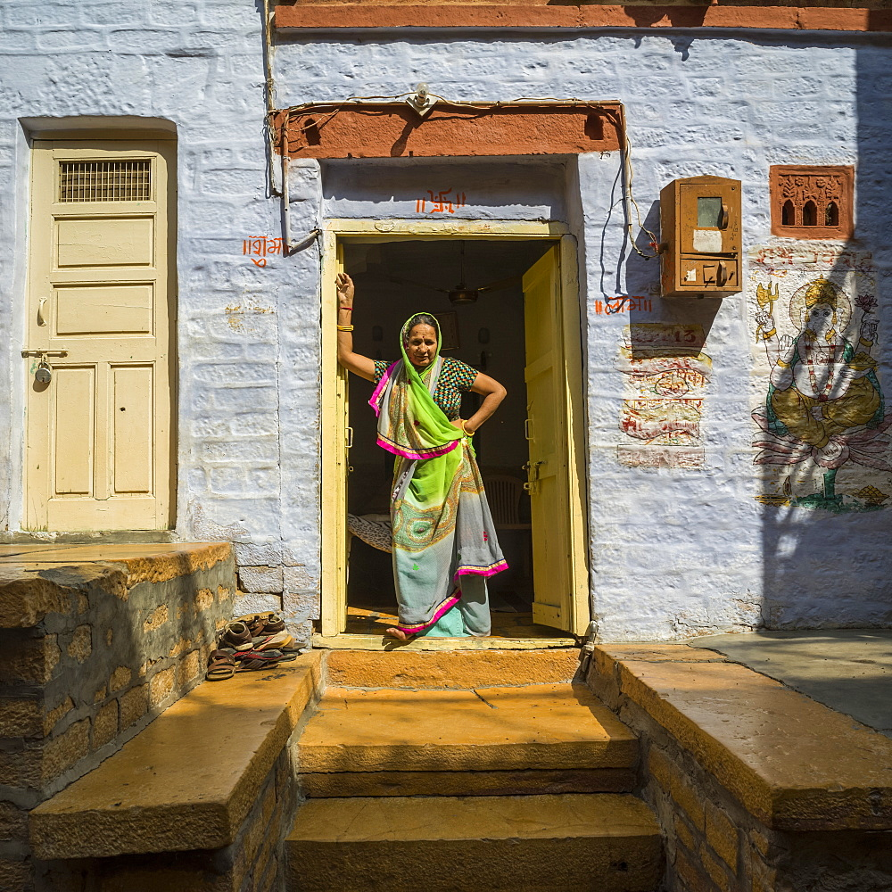 An Indian woman stands in the doorway of her home, Jaisalmer, Rajasthan, India