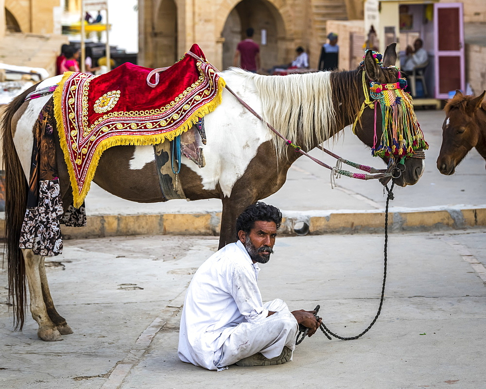 A man sits on the ground with his decorated horse standing beside him, Jaisalmer, Rajasthan, India