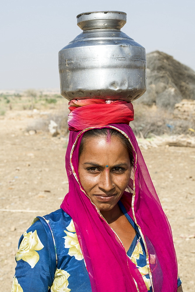 A woman carrying a jug on her head, Jaisalmer, Rajasthan, India
