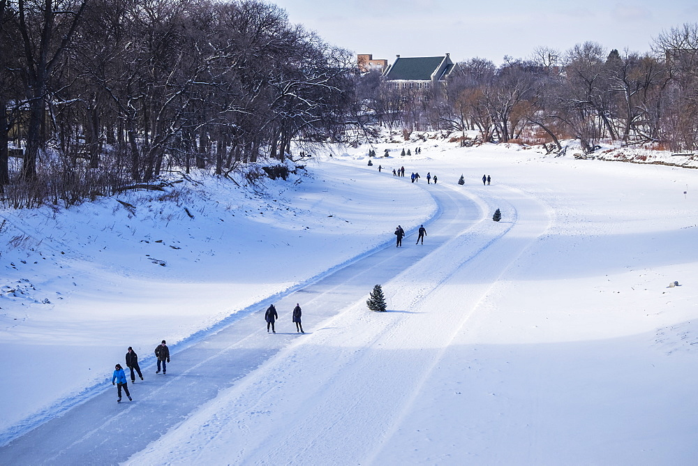 People walking and skating along the Red River Mutual Trail, Winnipeg, Manitoba, Canada
