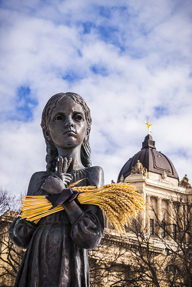 """Bitter Memories of Childhood"" is a memorial statue on the Manitoba Legislative Grounds which pays tribute to the 1932-1933 Ukrainian Famine and Genocide under Soviet ruler Joseph Stalin. The Legislative Building and the Golden Boy are seen in the backgro"