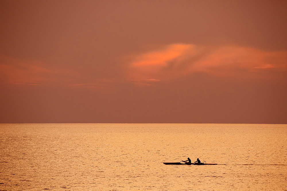 Two people in outrigger canoe at sunset, Kihei, Maui, Hawaii, United States of America