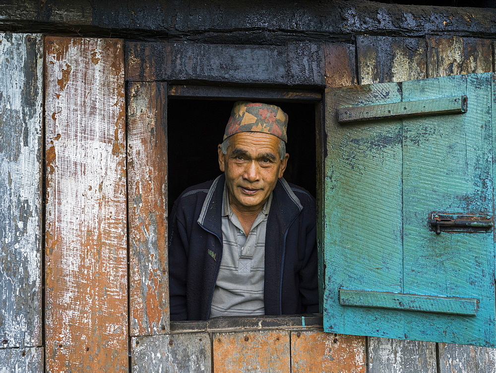 Portrait of an Indian man looking out a window, Radhu Khandu Village, Sikkim, India