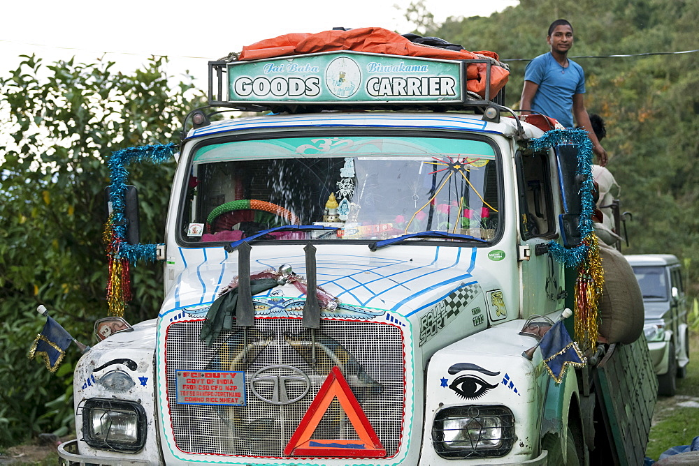 A colourful and decorated transport truck on a road with a worker standing up in the back, Sikkim, India