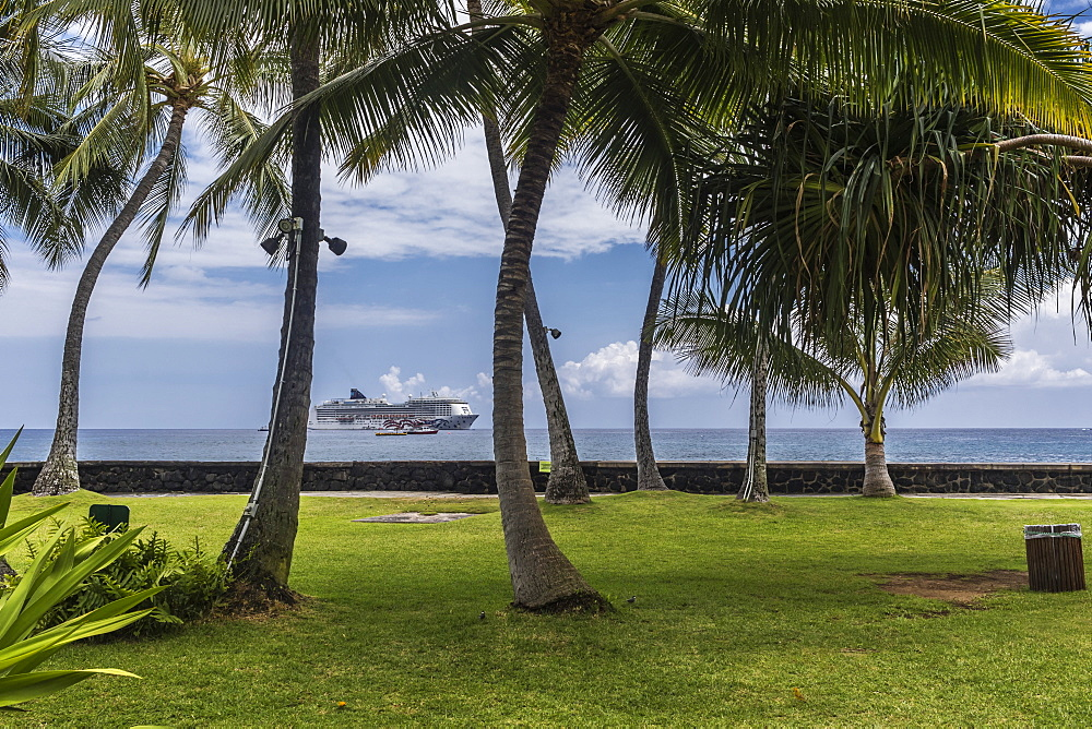 View of anchored vessels in Kailua Bay through a grove of coconut palm trees (Cocos nucifera) growing on the well-manicured Hulihee Palace grounds in Kailua-Kona, the Big Island, Hawaii, USA during the summer. The large cruise vessel is the Norwegian Crui