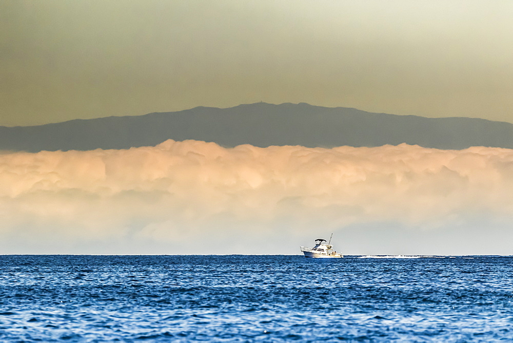 A sport fishing boat passes a morning fog bank off the Kona Coast, near Kailua on the Big Island, Hawaii during the summer, Island of Hawaii, Hawaii, United States of America