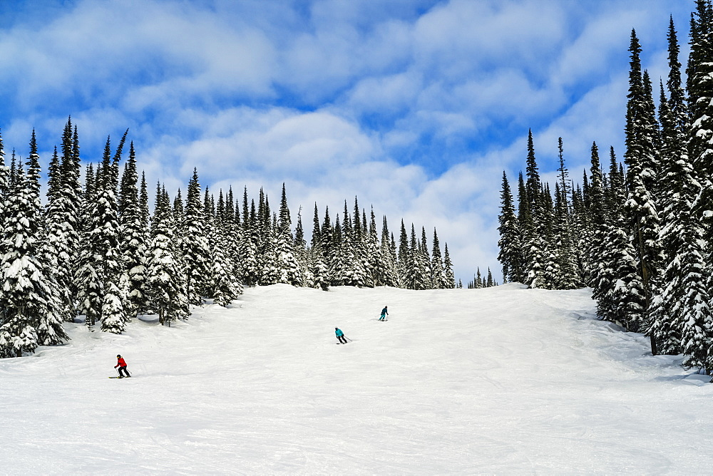 Skiers on a run at Sun Peaks ski resort, Kamloops, British Columbia, Canada