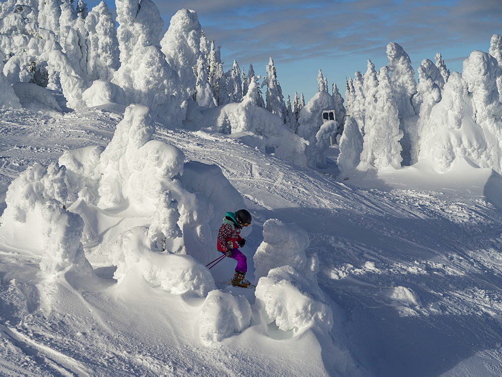 A young girl downhill skiing through the snow ghosts on a ski run at a ski resort, Kamloops, British Columbia, Canada