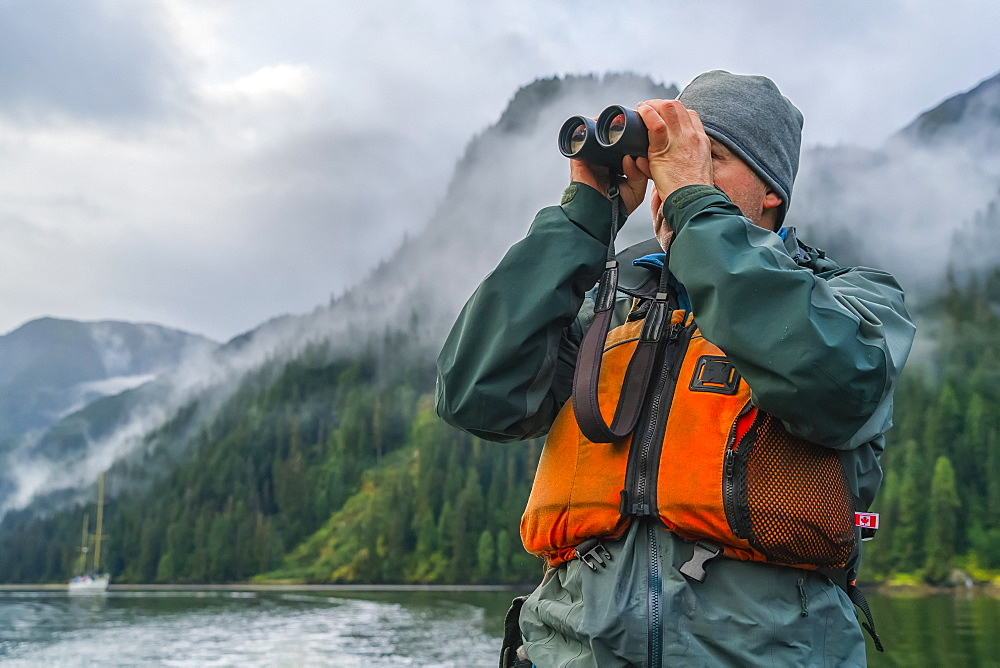 Man looking through a pair of binoculars with his sailboat in the distance, Great Bear Rainforest, Hartley Bay, British Columbia, Canada
