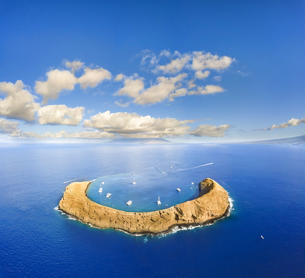 Molokini Crater, aerial shot of the crescent shaped islet at mid-morning with charter boats, Kihei, Maui, Hawaii, United States of America