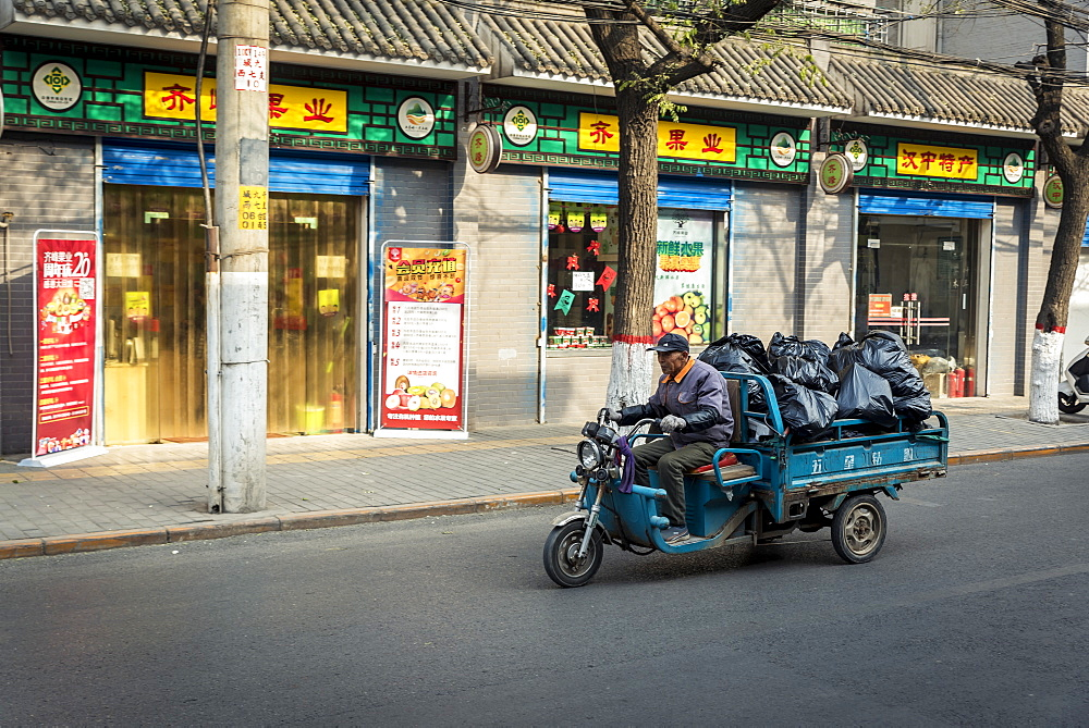 Vehicle carrying big, black plastic bags, Xian, Shaanxi Province, China