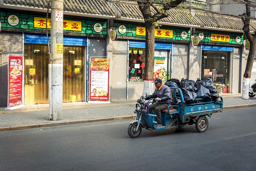 Vehicle carrying big, black plastic bags, Xian, Shaanxi Province, China