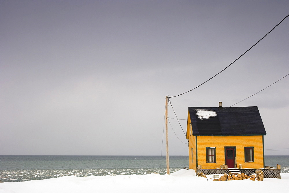 Small Yellow House On The Water's Edge In Winter, Quebec, Canada