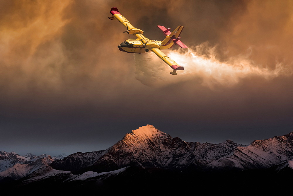 An aircraft dropping water on a forest fire in the mountains below, composite image