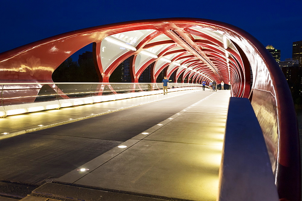 Glowing lights inside a pedestrian red metal bridge at night, Calgary, Alberta, Canada