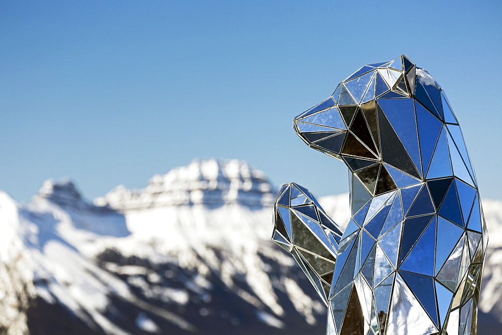 Close-up of mirrored bear sculpture with snow-covered mountain and blue sky in the background, Banff National Park, Banff, Alberta, Canada
