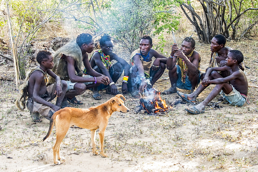 Hadzabe hunters and their dog gather around a campfire after a successful morning hunt near Lake Eyasi, Tanzania